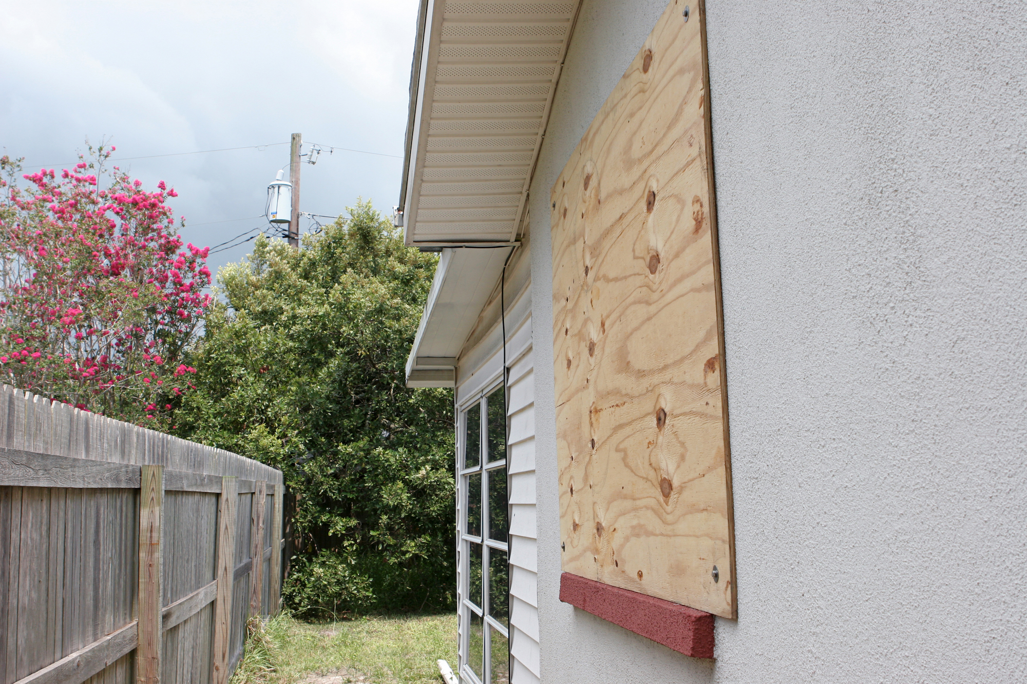 A home with plywood covering the window in preparation for a hurricane.