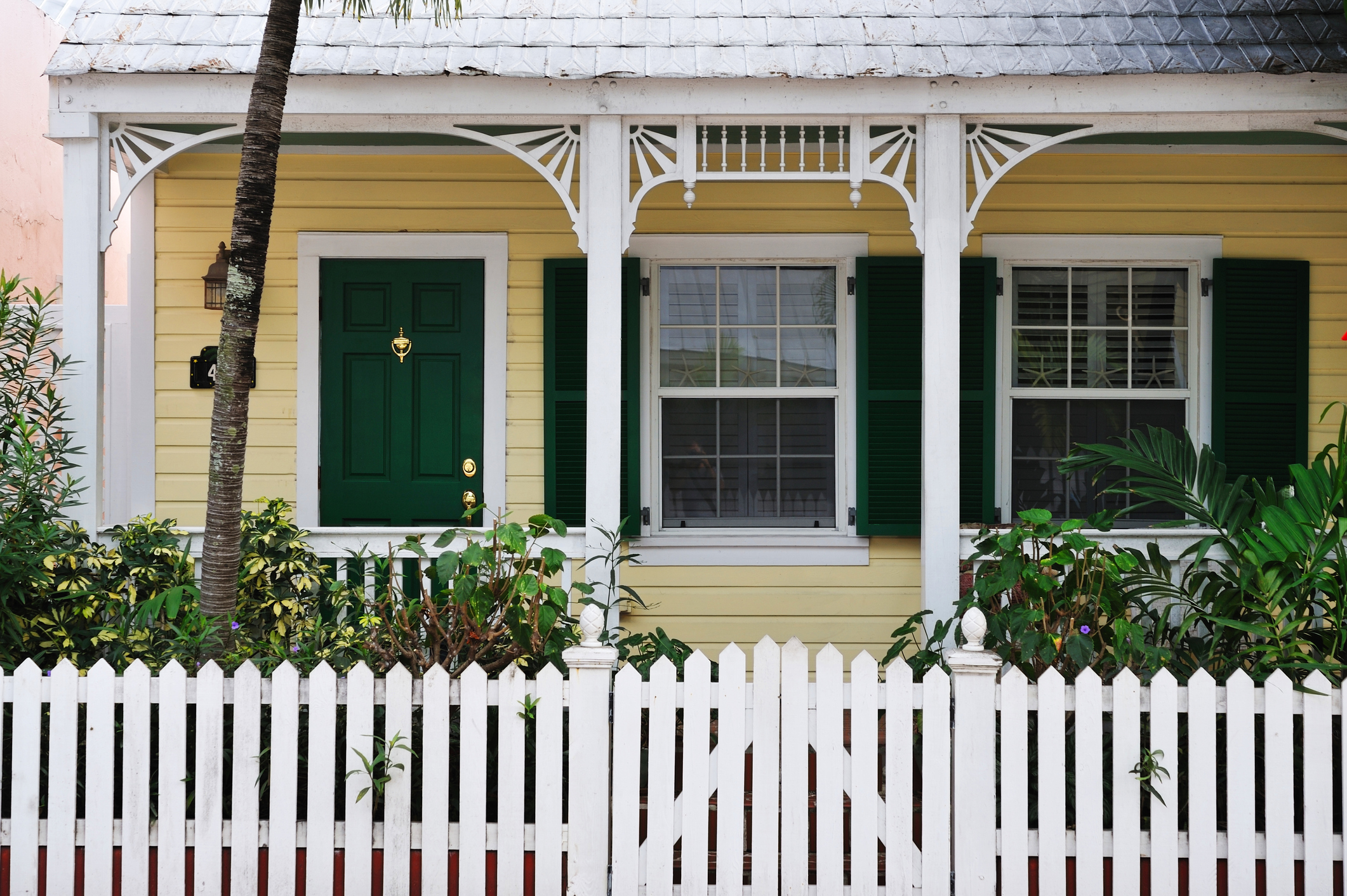 Tropical cottage with Bahama Shutters that offers protection and beauty