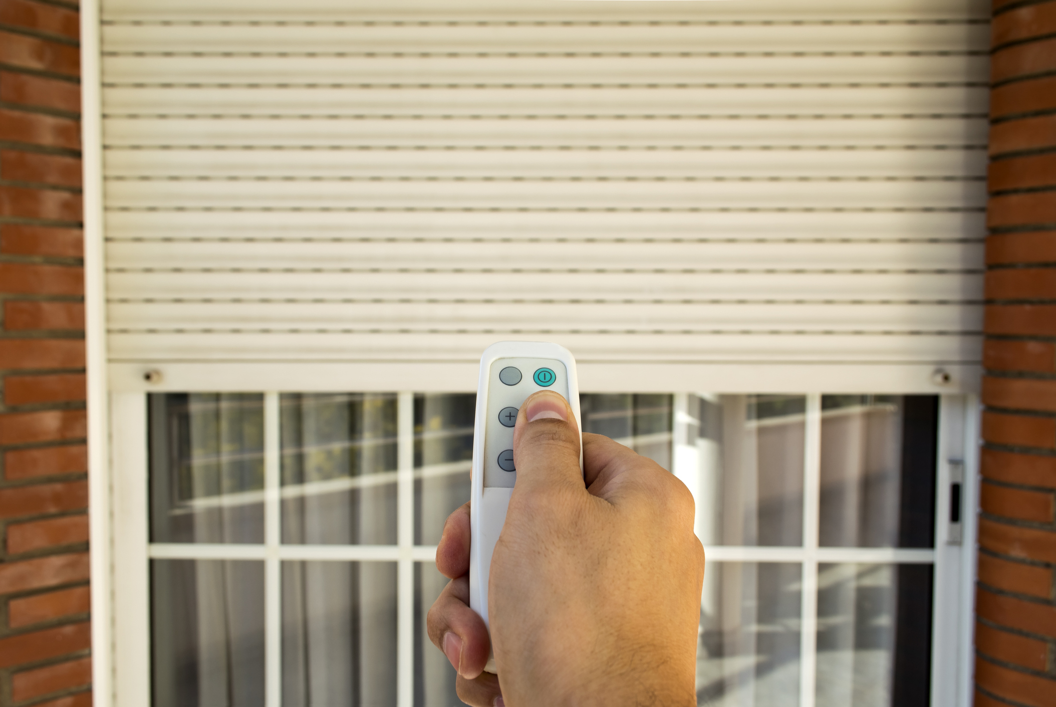 hand pressing a remote control with an electric roller shutter for home security