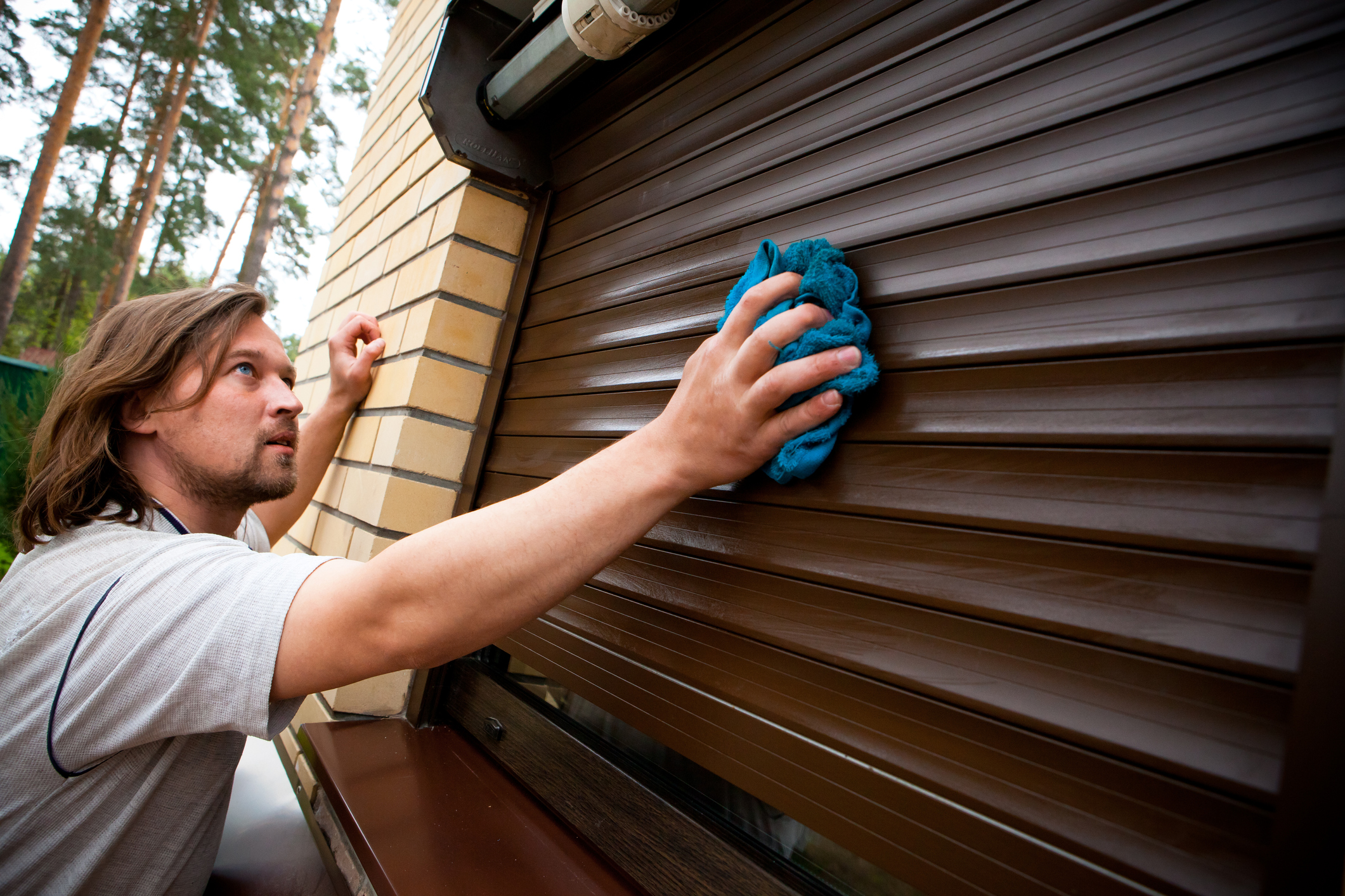 Man cleaning roll-up shutters