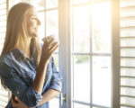 Young woman drinking coffee and looking through window as she considers roll-up shutters
