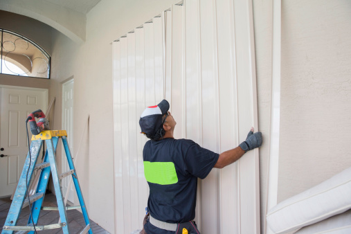 Contractor instaliing accordion shutters